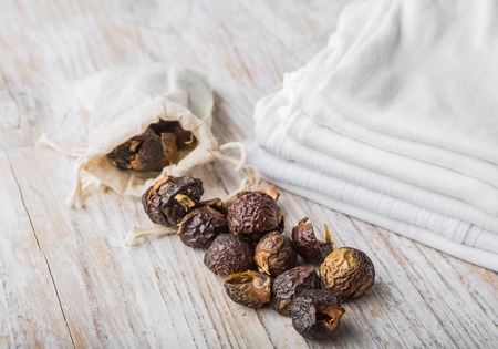 nutshells: Nutshells of soapnuts in a cotton bag for laundry on a white wood