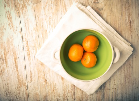 lomography: Vintage photo of tangerines in a bowl on a white wood