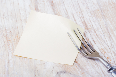 Blank picture frame paper with fork on a wooden table photo