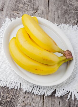 white plate: bananas on a white plate on old wooden table