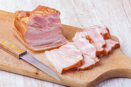 raw bacon: Raw bacon on a wooden plate