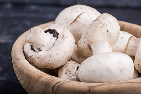 button mushrooms: Fresh whole white button mushrooms in wooden bowl on black table
