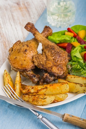 canard: duck leg with roasted potatoes and fruit salsa Stock Photo