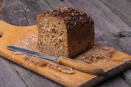 Homemade wholemeal bread on wooden table with knife photo