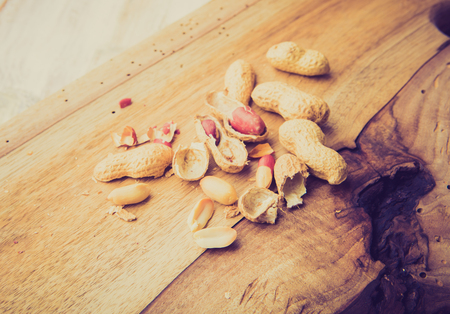lomography: Vintage photo of peanuts on the old kitchen board Stock Photo