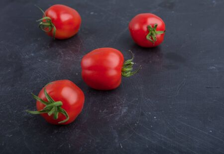 domates: Ripe red tomatoes on black table, studio shot