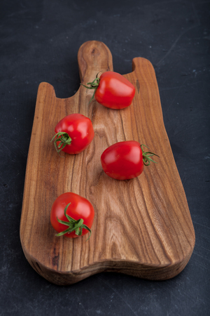 domates: Ripe red tomatoes on cutting board on black table, studio shot Stock Photo