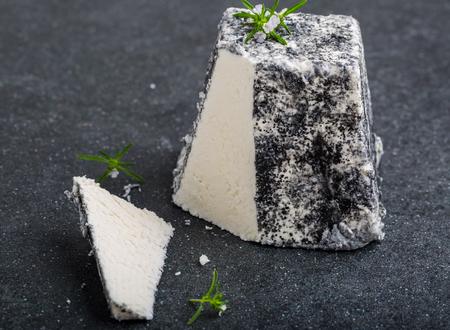 queso de cabra: Queso de cabra Valençay en Francia sobre un fondo negro Foto de archivo