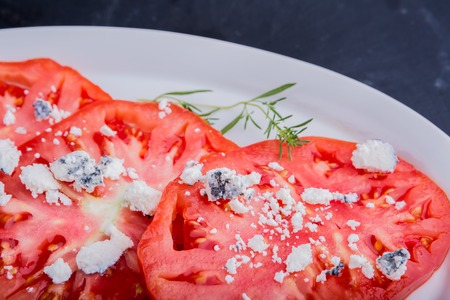 queso de cabra: salad with tomatoes with goat cheese on white plate