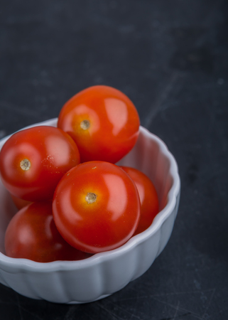Red cherry tomatoes in white bowl on black table
