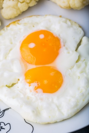 fried eggs: Two fried Eggs on a white plate, studio shot Stock Photo
