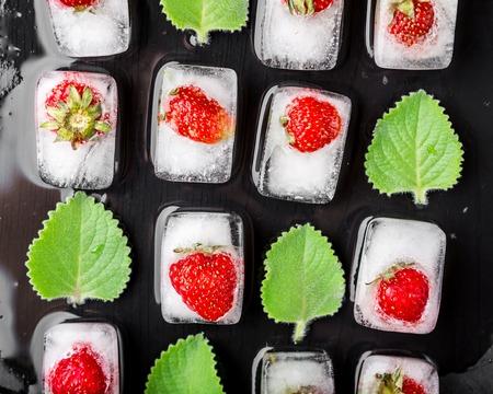 alimentos congelados: Cubos de hielo con fresas y hojas de menta fresca en el vector negro