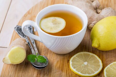catarrh: Ginger tea with lemon on a wooden table, studio shot