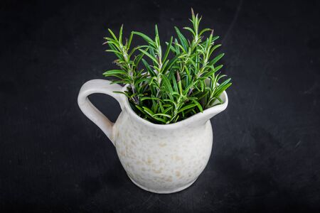 sprigs: Sprigs of fresh rosemary in a jug on black background