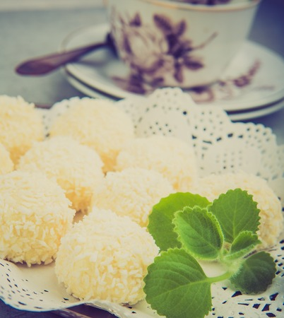 desiccated: Vintage photo of homemade coconut pralines on plate with mint leaf