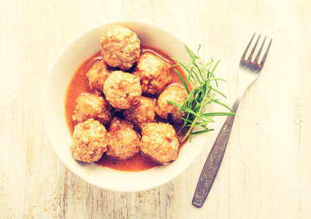 Vintage photo of bowl with meatballs and tomato sauce