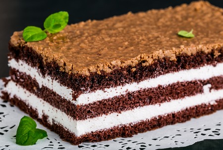 layer cake: Slice of chocolate cake stuffed with whipped cream and crunchy topping Stock Photo