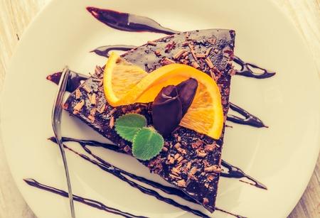 Vintage photo of espresso cake with chocolate glaze and fresh orange