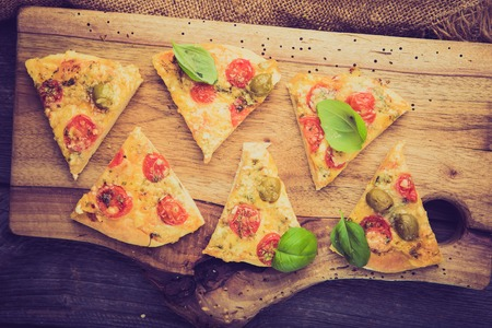 lomography: Vintage photo of pizza with tomatoes, olives and cheese on wooden board Stock Photo