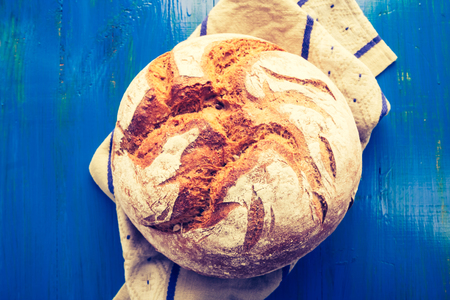 cros: Vintage photo of rustic sourdough bread on a linen cloth on blue wooden table Stock Photo