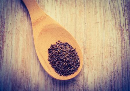 cros: Vintage photo of cumin on wooden spoon