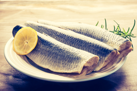 cros: Vintage photo of raw herrings fillets with lemon and rosemary