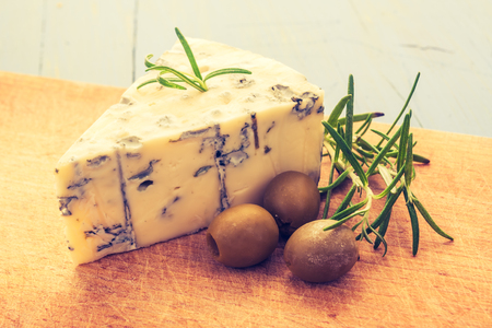 Vintage photo of blue cheese with olives on wooden board