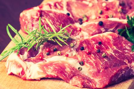 cros: Vintage photo of raw pork chops on wooden board
