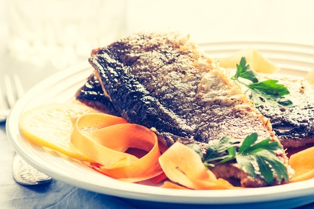 lomography: Vintage photo of fried herring with parsley on salad with carrots Stock Photo
