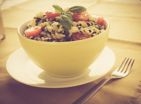 lomography: Vintage photo of pasta with spinach and cherry tomatoes.