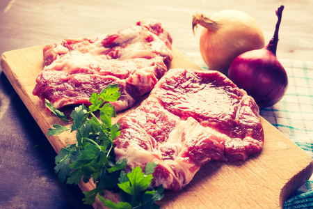 lomography: Vintage photo of raw pork chops on wooden board
