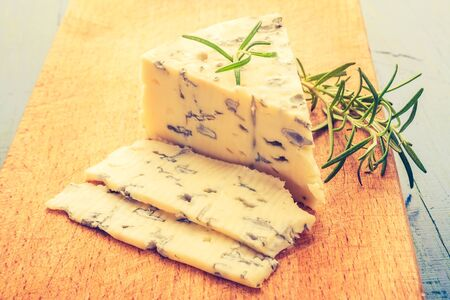 cros: Vintage photo of blue cheese on wooden board
