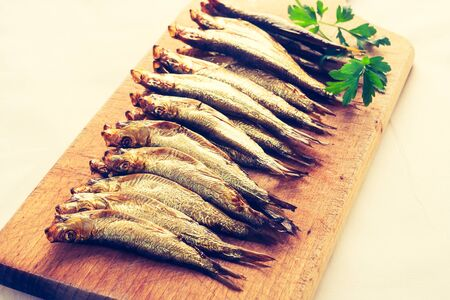 cros: Vintage photo of smoked sprats on cutting board