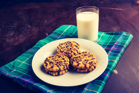 lomography: Vintage photo of cookies with milk on table Stock Photo