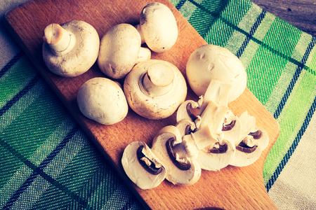 lomography: Vintage photo of fresh mushrooms on cutting board