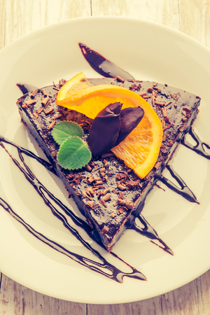 cros: Vintage photo of espresso cake with chocolate glaze and fresh orange