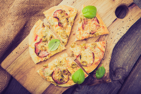 lomography: Vintage photo of homemade pizza with cheese, sausage, mushrooms and basil leaves