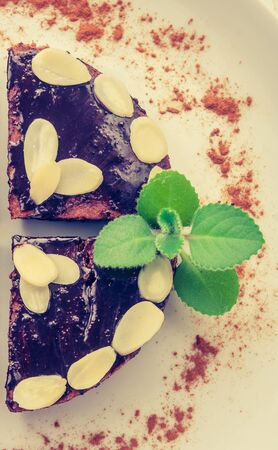 Vintage photo of chocolate cake with almonds and fresh mint