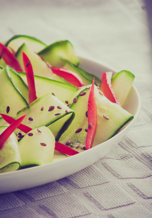 cros: Vintage photo of salad with cucumber, paprika and linseed