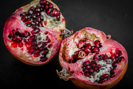 medium close up: Fresh juicy pomegranates on black wooden table