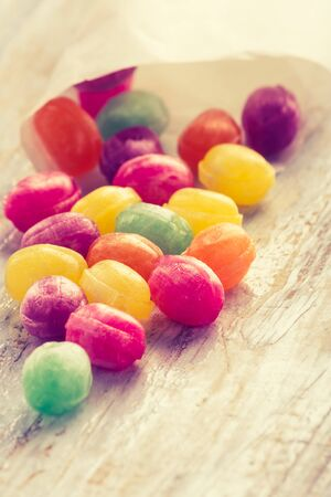 cros: Vintage photo of colorful candies on wooden table