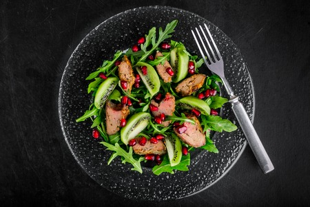 chicken liver: Salad appetizer with chicken liver, arugula, kiwi and pomegranate