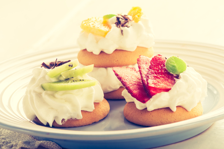 lomography: Vintage photo of small biscuits with fruits and whipped cream
