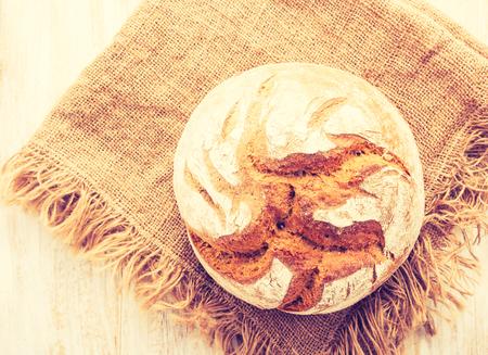 cros: Vintage photo of rustic sourdough bread on a linen cloth