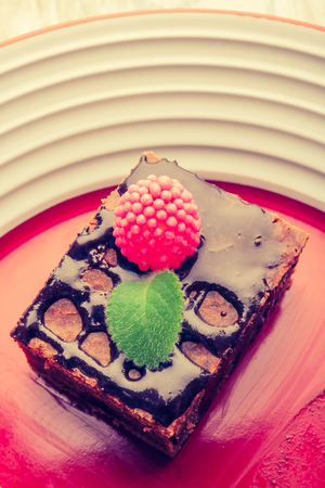 cros: Vintage photo of chocolate cake with raspberries and fresh mint. Stock Photo