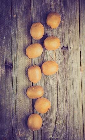 lomography: Vintage photo of fresh kiwi fruits on old wooden table