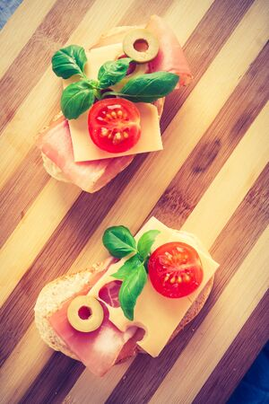 lomography: Vintage photo of small sandwiches with smoked ham, cheese and cherry tomato