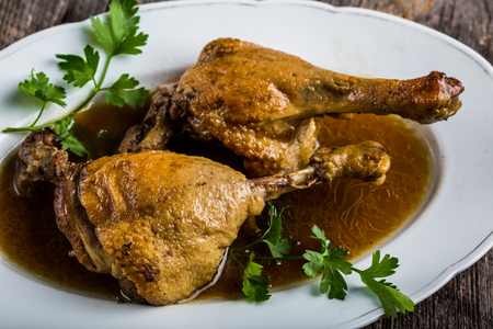 sause: Roasted duck legs in sause on white plate