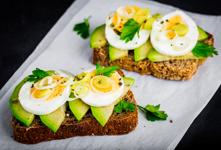 breakfast eggs: Sandwich with fresh green avocado, egg and leek Stock Photo