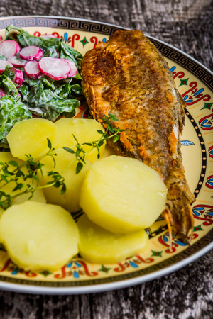 Fried roach served with potatoes and salad on old wooden table